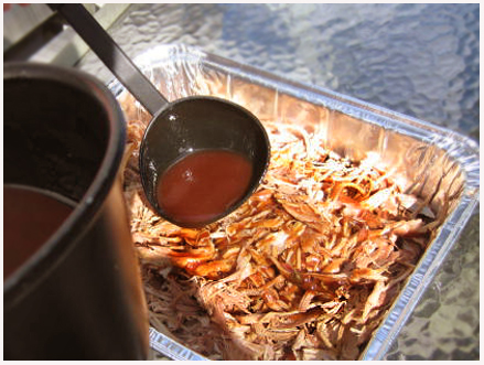 Adding vinegar sauce to pulled pork