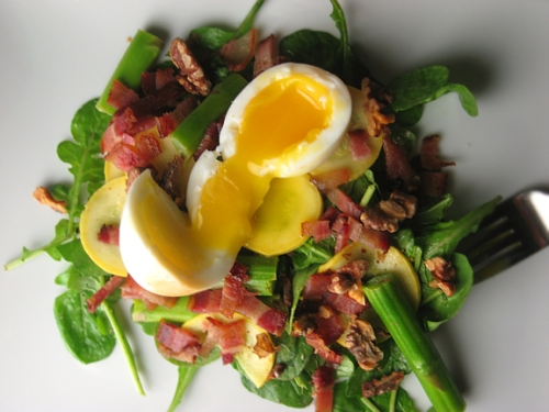 Runny egg, bacon, and vegetable salad